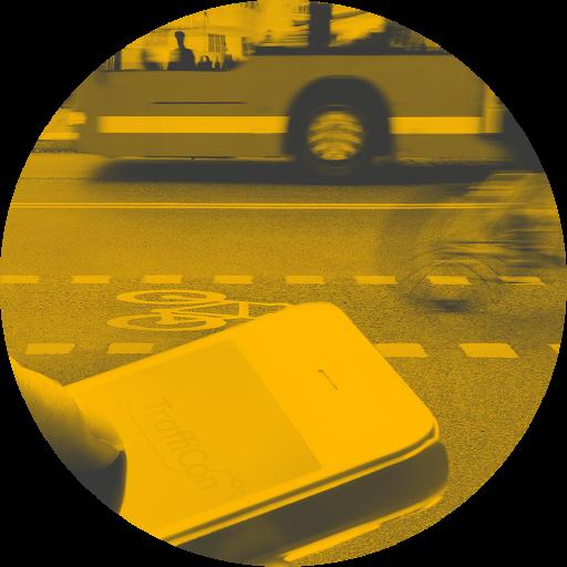 Straße mit Auto, Radfahrer, Bus und davor Hand die Smartphone bedient