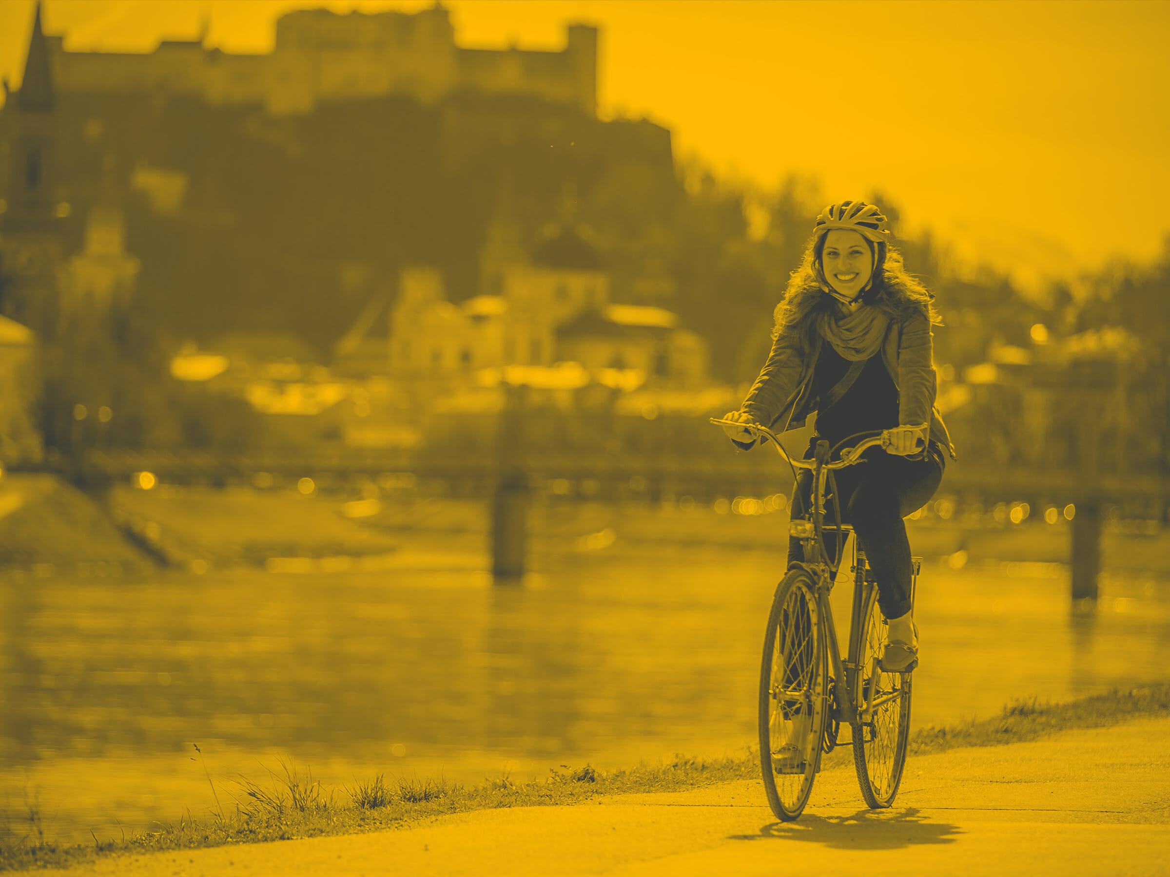 Judith Draschl fährt Rad am Salzachweg mit Ausblick auf die Festung