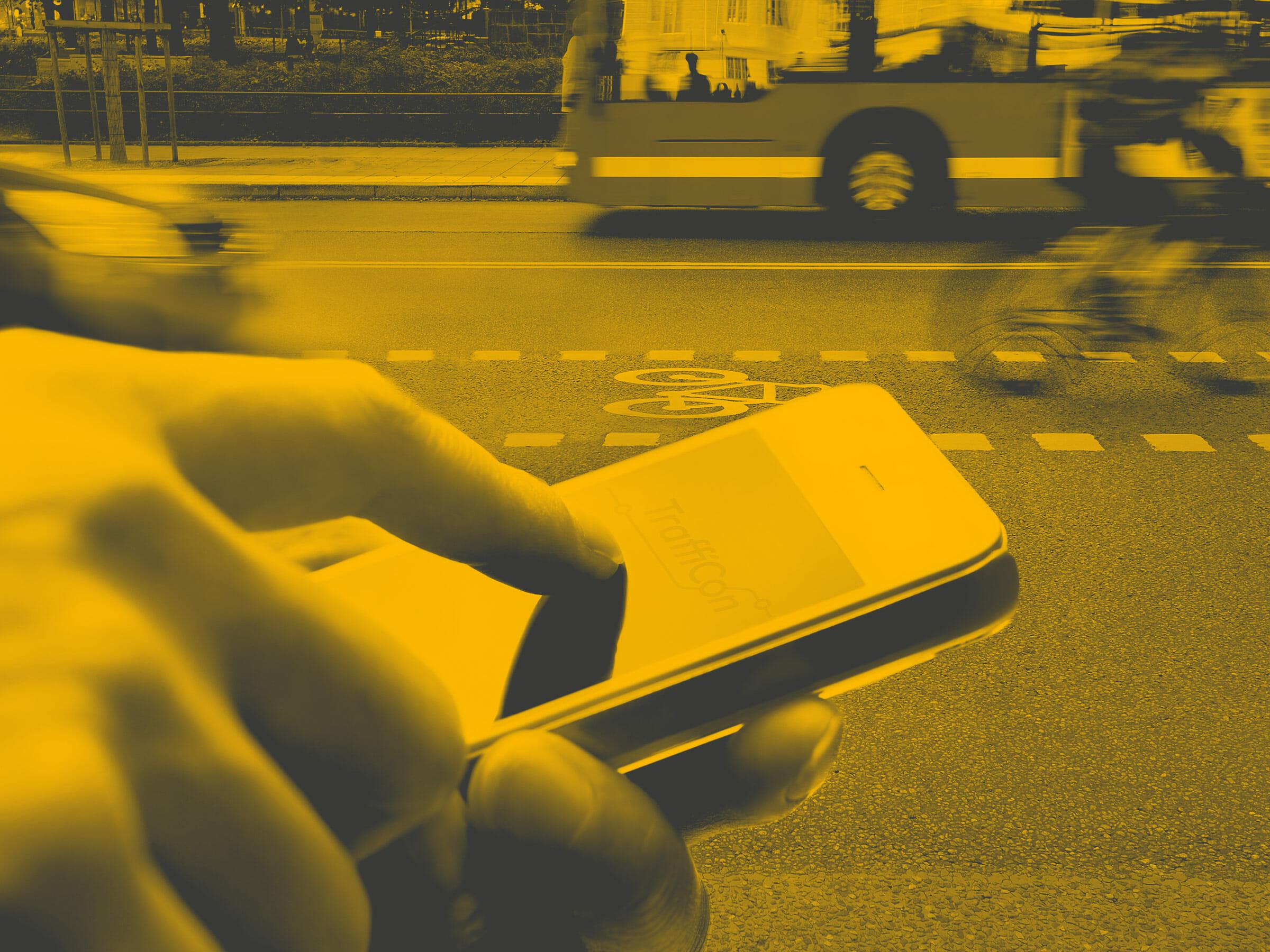 Hand die Smartphone bedient, Straße mit Radfahrer, Auto und Bus im Hintergrund
