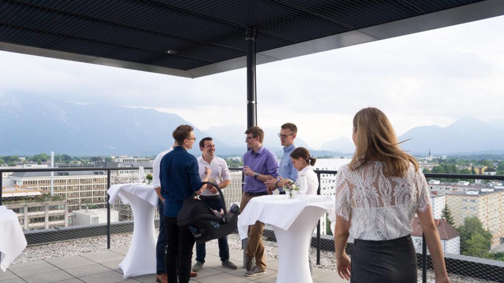 Das Trafficon Team auf der Dachterrasse mit Blick auf die Berge Salzburgs