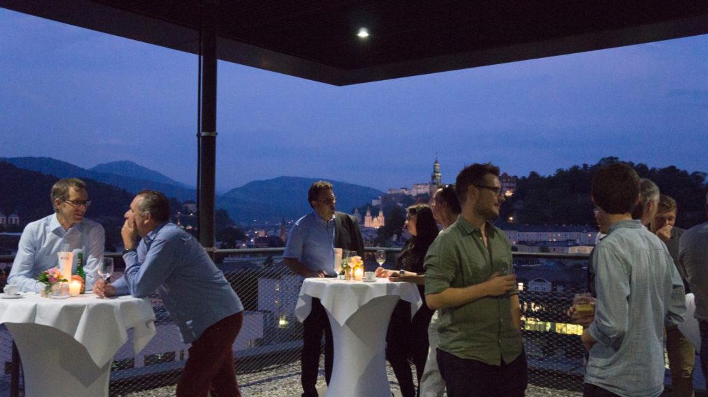 Gäste vor beleuchteter Altstadt in Abendstimmung